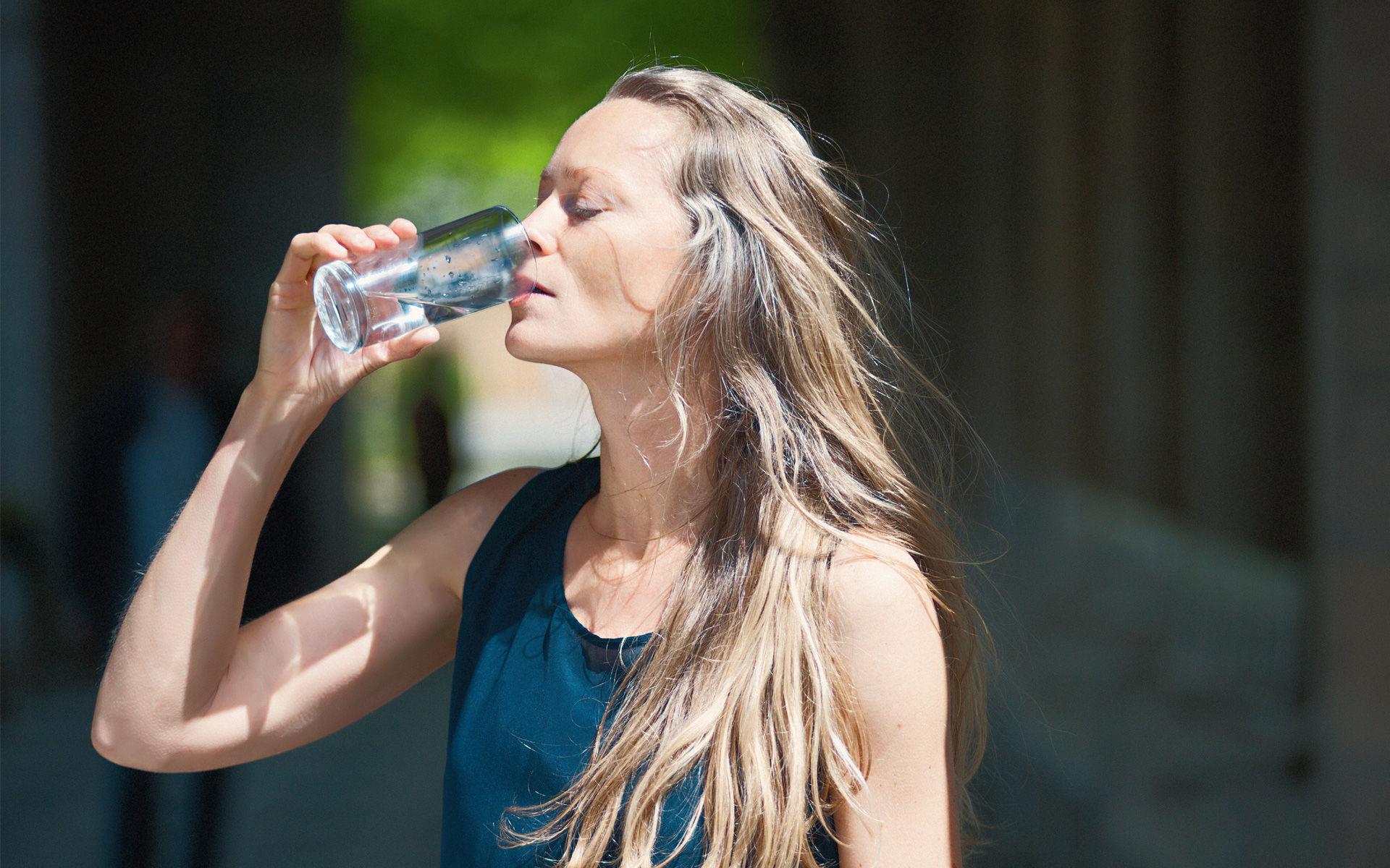 Frau trinkt Heilwasser aus Bad Kissingen