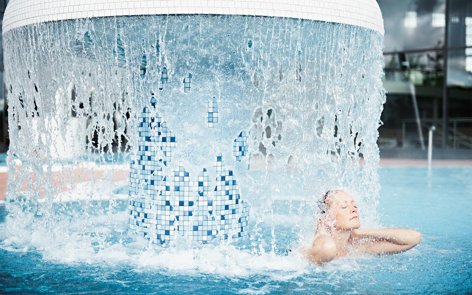 Foto einer Frau unter dem Wasserpilz in der KissSalis Therme in Bad Kissingen