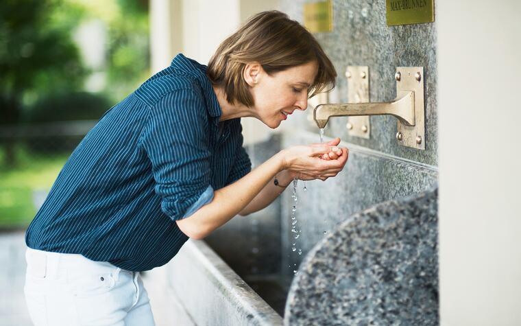 Frau trinkt Heilwasser vom Max-Brunnen in Bad Kissingen
